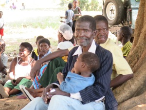 A grandfather waiting to learn about health and sanitation to help keep his grandson healthy.