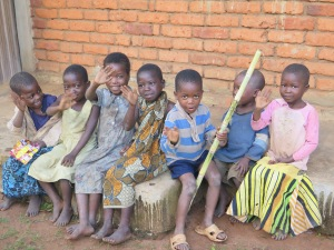 Children sharing a stick of sugarcane while waiting to hear about proper health practices.