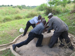 Everyone assisting to loosen the ring on the borehole pump